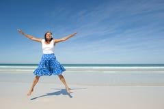 Ευτυχής παραλία γυναικών άλματος ώριμη Στοκ εικόνα με δικαίωμα ελεύθερης χρήσης