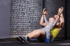Ευτυχής πατέρας και λίγος γιος που ασκούν με τα gimnastic δαχτυλίδια και που χαμογελούν ενάντια στο τουβλότοιχο στη γυμναστική Στοκ Εικόνες