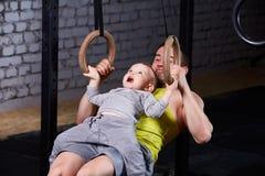 Ευτυχής πατέρας και λίγος γιος που ασκούν με τα gimnastic δαχτυλίδια και που χαμογελούν ενάντια στο τουβλότοιχο στη γυμναστική Στοκ φωτογραφίες με δικαίωμα ελεύθερης χρήσης