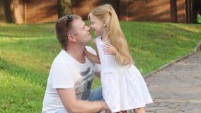 Ευτυχής πατέρας και οι μικρές μύτες τριψίματος κορών του στο θερινό ηλιόλουστο πάρκο φιλμ μικρού μήκους