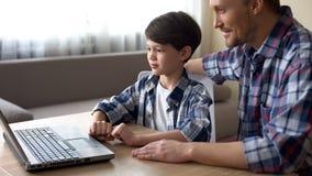 Ευτυχής πατέρας και ο γιος του που ψωνίζουν on-line στο φορητό προσωπικό υπολογιστή, τεχνολογίες στοκ εικόνες