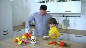 Ευτυχής πατέρας και πολύ χαριτωμένο αγόρι που προετοιμάζουν τη φυτική σαλάτα στην κουζίνα Σε αργή κίνηση Ευτυχής οικογένεια που π απόθεμα βίντεο