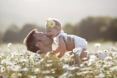 Ευτυχής πατέρας με λίγη κόρη που παίζει το καλοκαίρι σε έναν τομέα των άσπρων μαργαριτών Στοκ εικόνα με δικαίωμα ελεύθερης χρήσης
