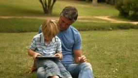 Ευτυχής πατέρας με το γιο του που χρησιμοποιεί την ταμπλέτα στο πάρκο απόθεμα βίντεο