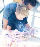 Ευτυχής πατέρας με το νέο γιο που χρησιμοποιεί το PC ταμπλετών στο ηλιόλουστο δωμάτιο Παίζοντας στήριξη υπολογιστών μπαμπάδων και Στοκ φωτογραφία με δικαίωμα ελεύθερης χρήσης