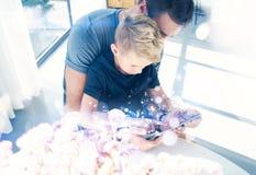 Ευτυχής πατέρας με το νέο γιο που χρησιμοποιεί το PC ταμπλετών στο ηλιόλουστο δωμάτιο Μπαμπάς και μικρό παιδί που παίζουν τον κιν Στοκ φωτογραφίες με δικαίωμα ελεύθερης χρήσης