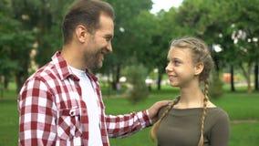 Ευτυχής πατέρας που αγκαλιάζει την όμορφη νέα κόρη του, που χαμογελά στη κάμερα, οικογένεια απόθεμα βίντεο