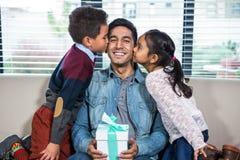 Ευτυχής πατέρας που λαμβάνει ένα δώρο από τα παιδιά του στοκ εικόνα με δικαίωμα ελεύθερης χρήσης