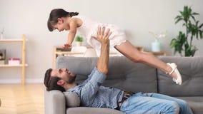 Ευτυχής πατέρας που βρίσκεται στην ανυψωτική κόρη παιδιών καναπέδων που έχει τη διασκέδαση απόθεμα βίντεο