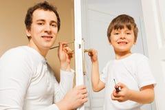 Ευτυχής πατέρας που διδάσκει το γιο του για να καθορίσει door-handle στοκ εικόνες