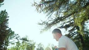 Ευτυχής πατέρας που ρίχνει επάνω στη μικρή κόρη του στο θερινό πάρκο με τη φλόγα φακών απόθεμα βίντεο