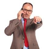 Ευτυχής παλαιός επιχειρηματίας που μιλά στο τηλέφωνο και που δείχνει το δάχτυλο Στοκ εικόνα με δικαίωμα ελεύθερης χρήσης