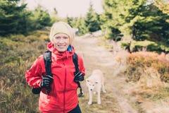 Ευτυχής πεζοπορία γυναικών που περπατά με το σκυλί στο δάσος φθινοπώρου Στοκ Φωτογραφίες