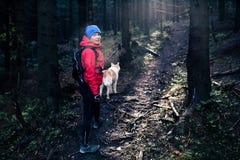 Ευτυχής πεζοπορία γυναικών που περπατά με το σκυλί Στοκ Φωτογραφίες