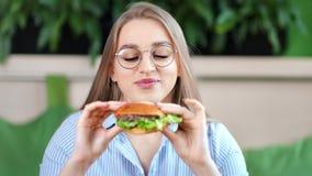 Ευτυχής πεινασμένη νέα όμορφη γυναίκα κινηματογραφήσεων σε πρώτο πλάνο που δαγκώνει ορεκτικό φρέσκο burger που εξετάζει τη κάμερα απόθεμα βίντεο