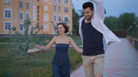 Ευτυχής περίπατος διασκέδασης ζευγών newlyweds κατά μήκος του περιπάτου κοντά στο νέο σπίτι του φιλμ μικρού μήκους