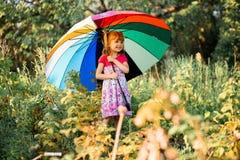 Ευτυχής περίπατος κοριτσιών παιδιών με την πολύχρωμη ομπρέλα κάτω από τη βροχή στοκ φωτογραφία