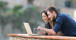 Ευτυχής περιεκτικότητα σε lap-top ξεφυλλίσματος ζευγών σε ένα μπαλκόνι απόθεμα βίντεο