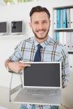 Ευτυχής περιστασιακός επιχειρηματίας που δείχνει το lap-top Στοκ Εικόνα