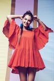Ευτυχής περιστροφή γυναικών στο πορτοκαλί φόρεμα στο πολυ υπόβαθρο στοκ εικόνα