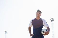 Ευτυχής ποδοσφαιριστής που στέκεται με μια σφαίρα Στοκ Φωτογραφίες