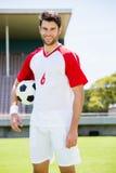 Ευτυχής ποδοσφαιριστής που στέκεται με μια σφαίρα Στοκ φωτογραφία με δικαίωμα ελεύθερης χρήσης