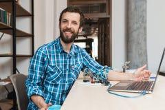 Ευτυχής προγραμματιστής που χαμογελά στη κάμερα κοντά στο lap-top Στοκ Φωτογραφία