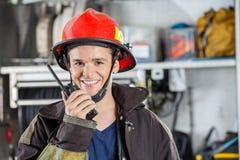 Ευτυχής πυροσβέστης που χρησιμοποιεί την ομιλούσα ταινία Walkie Στοκ φωτογραφία με δικαίωμα ελεύθερης χρήσης