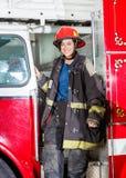 Ευτυχής πυροσβέστης στην ομοιόμορφη στάση στο φορτηγό Στοκ Φωτογραφία