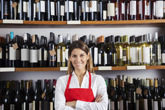 Ευτυχής πωλήτρια που στέκεται ενάντια στα ράφια στο κατάστημα κρασιού Στοκ Φωτογραφία