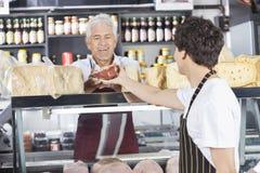 Ευτυχής πωλητής που λαμβάνει το τυρί από το συνάδελφο στο κατάστημα παντοπωλείων Στοκ εικόνες με δικαίωμα ελεύθερης χρήσης