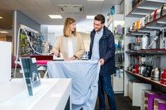 Ευτυχής σίδηρος δοκιμής ζεύγους με το σιδέρωμα του πουκάμισου στην υπεραγορά στοκ εικόνες