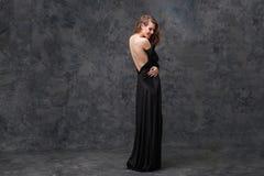 Ευτυχής σαγηνευτική γυναίκα στο μακρύ φόρεμα βραδιού με την ανοικτή πλάτη Στοκ Φωτογραφία