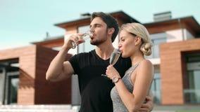 Ευτυχής σαμπάνια κατανάλωσης ζευγών κοντά στο σπίτι πολυτέλειας Εραστές κινηματογραφήσεων σε πρώτο πλάνο που πίνουν το κρασί απόθεμα βίντεο