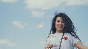 Ευτυχής σγουρός χορός brunette στη μουσική ενάντια στον ουρανό απόθεμα βίντεο