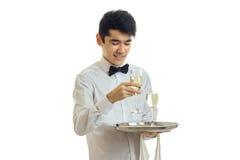 Ευτυχής σερβιτόρος νεαρών άνδρων σε ομοιόμορφο με δύο ποτήρια του κρασιού στο ασημένιο χαμόγελο δίσκων Στοκ Φωτογραφίες