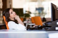 Ευτυχής σκεπτική επιχειρηματίας που προγραμματίζει και που εξετάζει λοξά το γραφείο στοκ εικόνες