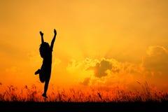 Ευτυχής σκιαγραφία άλματος και ηλιοβασιλέματος γυναικών την όμορφη ημέρα Στοκ Φωτογραφία