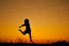 Ευτυχής σκιαγραφία άλματος και ηλιοβασιλέματος γυναικών Στοκ εικόνα με δικαίωμα ελεύθερης χρήσης