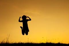 Ευτυχής σκιαγραφία άλματος και ηλιοβασιλέματος γυναικών Στοκ Εικόνες