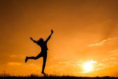 Ευτυχής σκιαγραφία άλματος και ηλιοβασιλέματος γυναικών Στοκ Φωτογραφία