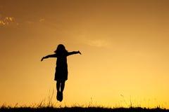 Ευτυχής σκιαγραφία άλματος και ηλιοβασιλέματος γυναικών Στοκ φωτογραφία με δικαίωμα ελεύθερης χρήσης