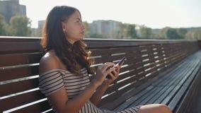 Ευτυχής σπουδαστής κοριτσιών που χρησιμοποιεί ένα έξυπνο τηλέφωνο σε μια συνεδρίαση πάρκων πόλεων σε έναν πάγκο, νέα εφαρμογή χρή απόθεμα βίντεο