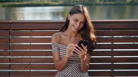 Ευτυχής σπουδαστής κοριτσιών που χρησιμοποιεί ένα έξυπνο τηλέφωνο σε μια συνεδρίαση πάρκων πόλεων σε έναν πάγκο, νέα εφαρμογή χρή φιλμ μικρού μήκους