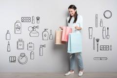 Ευτυχής σπουδαστής που εξετάζει την τσάντα εγγράφου της μετά από να αγοράσει τα αρώματα στοκ φωτογραφία