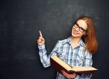 Ευτυχής σπουδαστής κοριτσιών με τα γυαλιά και βιβλίο από τον κενό πίνακα Στοκ Εικόνες