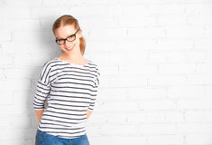 Ευτυχής σπουδαστής κοριτσιών στα γυαλιά σε έναν κενό άσπρο τουβλότοιχο Στοκ φωτογραφίες με δικαίωμα ελεύθερης χρήσης