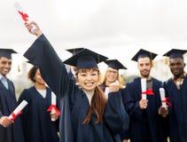 Ευτυχής σπουδαστής με τη βαθμολόγηση εορτασμού διπλωμάτων Στοκ Φωτογραφία