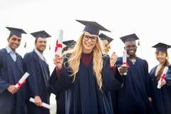 Ευτυχής σπουδαστής με τη βαθμολόγηση εορτασμού διπλωμάτων Στοκ Φωτογραφίες