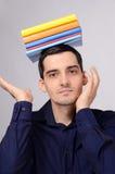 Ευτυχής σπουδαστής που κρατά έναν σωρό των βιβλίων στο κεφάλι του. Στοκ Εικόνες